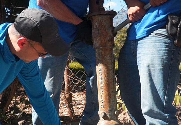 There men using a well drill
