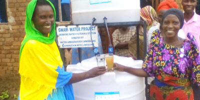 Two women in front of a sawyer filter system in Uganda comparing a glass of clean water with dirty water.