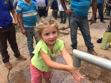 Young girl washing her hands.