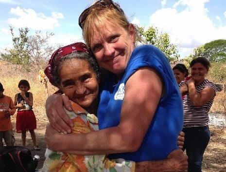 A volunteer hugging a local.